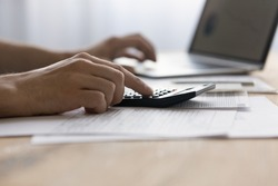 Close up man laptop and calculator, managing finances or planning budget, businessman calculating corporate bills, expenses, browsing online banking service, sitting at table with financial documents