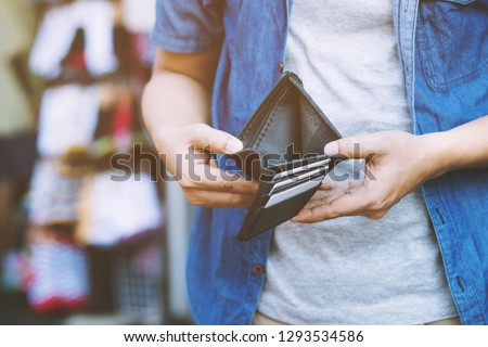 close up man person holding an empty wallet in the hands of an man no money out of pocket in front of the shop store. No money to pay shopping purchase Sell or Payment.