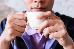 Close up man's hand holding white coffee cup on morning time.