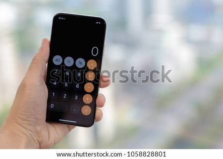 Close up man's hand open calculator app on his smartphone with blurred background. To start using calculator application. Technology Concept