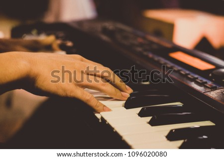Close-up man's hands playing the piano