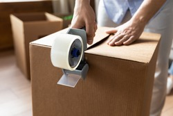 Close up man sealing cardboard box with adhesive tape, using dispenser, moving day and relocating delivery service concept, young male preparing to relocation, packing belongings, parcel