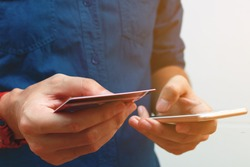Close up man using smart phone and holding credit card with shopping online. Online payment concept.