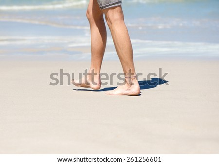 Close up man walking barefoot on white sand beach #261256601