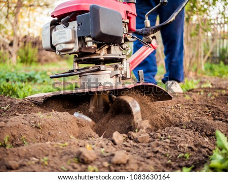 close up man with rotating cultivating tiller tractor in the garden