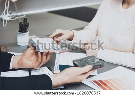 Close up manager in suit is showing different materials to female client in kitchen store. A woman chooses a new material for the kitchen while sitting at the table with the seller.  Foto stock ©