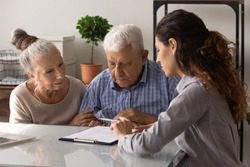 Close up manager realtor advisor consulting mature couple about contract terms at meeting, senior family involved in negotiations, making insurance or investment deal, purchasing real estate