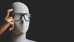 Close up mannequin with eyeglasses in thinking and having idea gesture on black background with film tone style