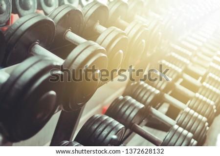Close up many metal dumbbells on rack in sport fitness center. Black dumbbell set.
