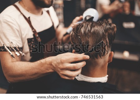 Close-up, master Barber does the hairstyle and styling with dryer, dries hair to guy. Concept Barbershop. Soft focus.
