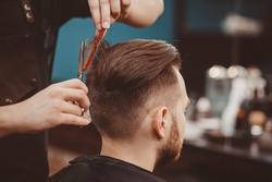 Close-up, master hairdresser does hairstyle and style with scissors and comb. Concept Barbershop.