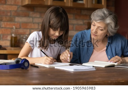 Close up mature grandmother helping to granddaughter with school assignment, focused little girl writing notes, older teacher training pupil, involved in lesson at home, homeschooling concept Foto stock ©