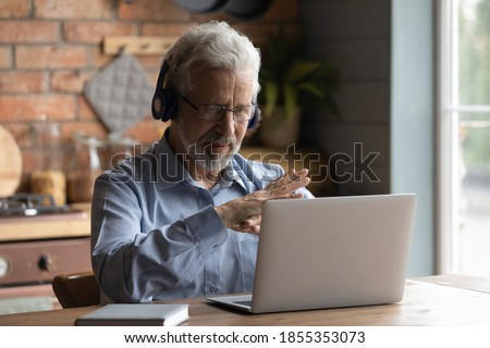 Close up mature man wearing headphones using laptop, making video call, sitting at table in kitchen, senior teacher mentor wearing glasses engaged online conference, recording webinar, teaching