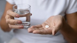 Close up mature woman hands hold pill and glass of natural clean water. Older generation female take analgetic painkiller drug. Painful old age, caring for health of senior citizen, daily meds concept