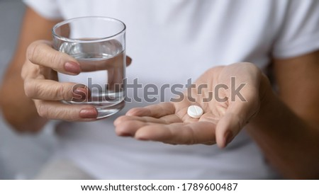 Close up mature woman hands hold pill and glass of natural clean water. Older generation female take analgetic painkiller drug. Painful old age, caring for health of senior citizen, daily meds concept Photo stock ©