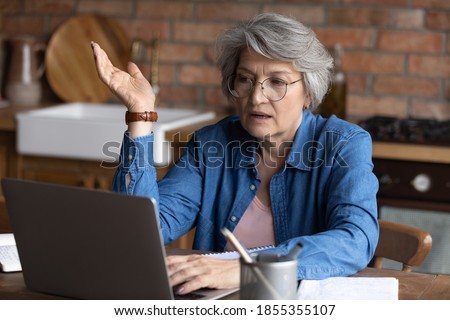 Close up mature woman wearing glasses making video call, using laptop, sitting at desk at home, confident senior businesswoman engaged in internet negotiations, teacher leading webinar online