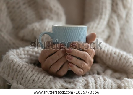 Close up mature woman wrapped warm blanket holding mug of coffee or tea, middle aged female enjoying free time, weekend at home, relaxing, drinking hot beverage in morning, starting new day