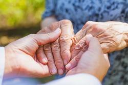 Close up medical doctor holding senior woman's shaking hands, Parkinson disease