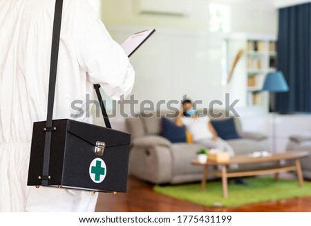 Close up medical staff in personal protective equipment PPE suit with background of asian woman with face mask waiting in living room of apartment .Delivery coronavirus covid-19 test at home concept.