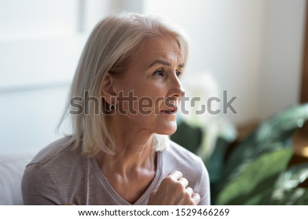 Close up melancholic 60s elderly woman looks away face lit by sunlight when feels hurt and lonely, pensive old female lost on sad thoughts, aging process, go through divorce personal problems concept