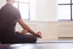 Close up men hands, back view. Young men do yoga indoors on black mat. Guy exercising yoga with a black background in gym. Young men meditating in lotus posture closeup.