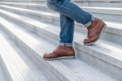 Close up Men wear jeans and shoe are walk down the concrete stairs. lifestyle men fashion