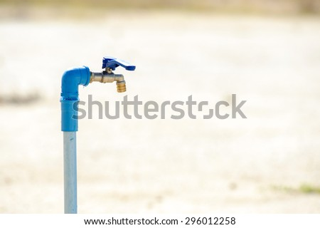 Close up metal blue water faucet on dry land. Water shortage concept.
