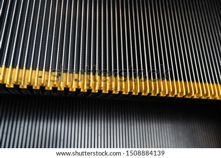 Close up metal escalator stairs with yellow plastic rubber anti-slip stair nosing.