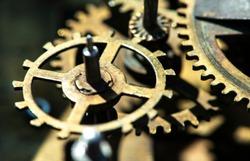 Close up metal gears mechanism. Golden colours. Hard light. Clock interior mechanism parts.