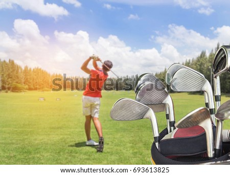 Close up metal golf clubs in bag with golfer during practice driving range in golf course yard signs background #693613825