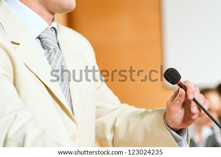 close-up microphone and business man, on the background of business communication at the conference