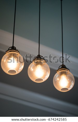 Close up mid century modern remodeled home dining living room ceiling chandelier with three hanging incandescent illuminated light bulb in glass globe orbs on black electrical cable with crown molding #674242585