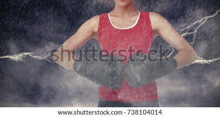 Close-up mid section of a determined female boxer against splashing of blue color powder #738104014