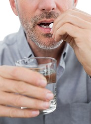 Close-up mid section of a man with glass of water and pill