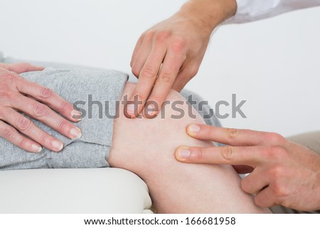Close-up mid section of a woman getting her knee examined at the medical office
