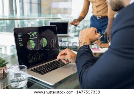 Close up mid-section of two young businessmen working in a modern office. A Caucasian businessman in sitting in the foreground using a laptop while his African American male colleague stands in the
