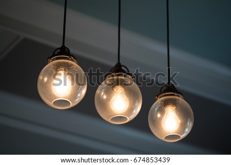 Close up midcentury modern remodeled home dining living room ceiling chandelier with three hanging incandescent illuminated light bulbs in glass globe orbs on black electrical cable with crown molding #674853439