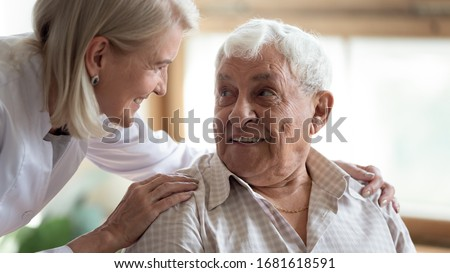Close up middle-aged female doctor supporting older patient, touching shoulders, giving psychological help, caring mature female wearing white uniform talking with elderly man, healthcare concept