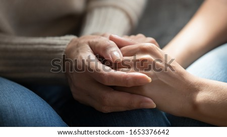 Close up middle aged mommys wrinkled hands holding young daughters, millennial woman supporting mature mum, showing care, love. Asking for apologize, forgiveness, reconcile after quarrel gesture.