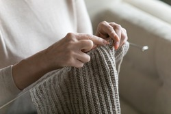Close up middle aged old woman holding knitting needles, enjoying creating warm clothing stuff with woolen material threads at weekend, leisure hobby activity pastime of elderly retired people.