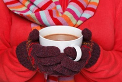 Close up midriff photo of a woman wearing a red jumper, woolen gloves and a scarf holding a mug full of hot chocolate, good image to convey a feeling of winter and warmth.