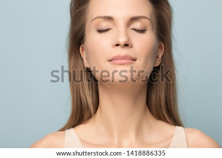 Close up millennial calm attractive woman inhaling fresh air, breathing, relaxing with closed eyes, meditating, visualizing future, reminding pleasant positive memories, isolated on studio background.