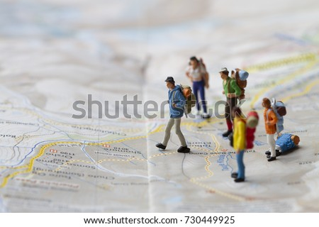 close up miniature backpack traveller start journey and waking on map adventure and tourist concept #730449925