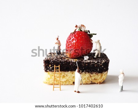 Close up miniature people on chocolate cake with fresh strawberry on top,cooking and decoration concept.