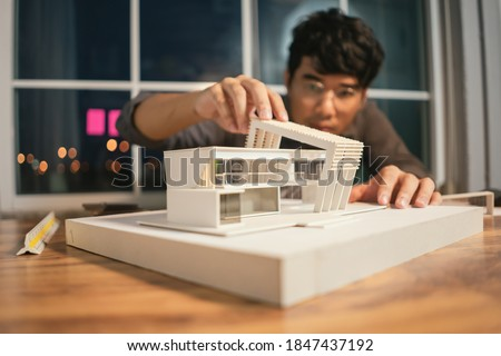 Close up model house modern style, Asian man architect making architecture model of house. Man architect working in the office.