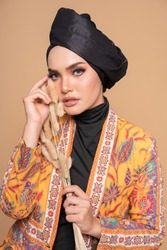 Close up model wearing modern kebaya with black turban, an Asian traditional dress for Muslim woman isolated over beige background. Stylish Muslim female hijab fashion lifestyle concept.
