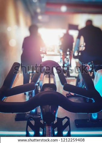 Close up modern Bike with blurred row of man and woman exercise bikes. Fitness cycling indoor concept. #1212259408