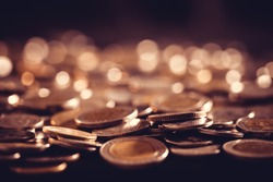 Close up money coin on the floor in dark light , business and financial for money saving or investment background concept with black copy space , extremely close up and shallow DOF