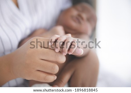 Close up Mother holding hands newborn baby in a room with a lot of sunlight, Newborn baby sleeping in the mother's embrace. Health care, love, relationship concept.