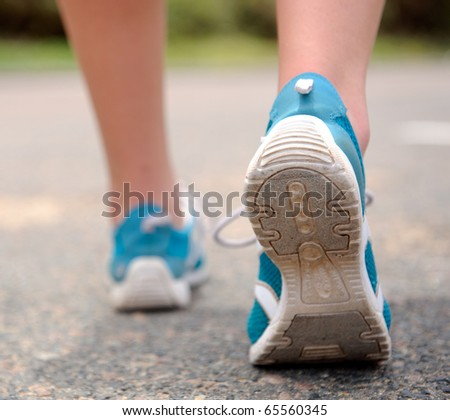 Close up motion shot of person walking away in running shoes - stock photo